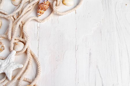 Sea shells with rope on white wooden background, copy space. Vacation concept Standard-Bild