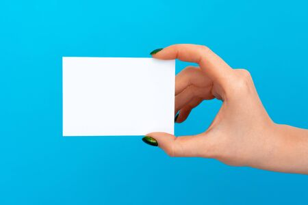 Woman hand holding blank card on blue background