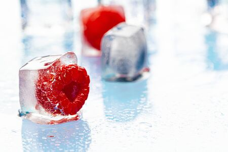 Frozen berries in ice cubes on pink Фото со стока