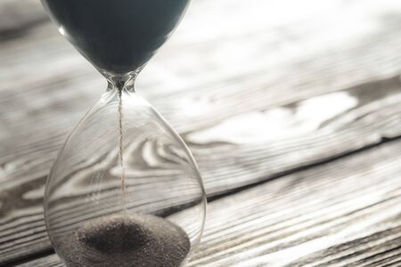 Modern hourglass on wooden background. Close up.