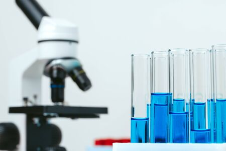 Microscope and colored test tubes on table in laboratory, close up