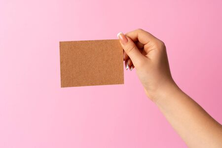 Woman hand showing blank business card on pink background. Close up.