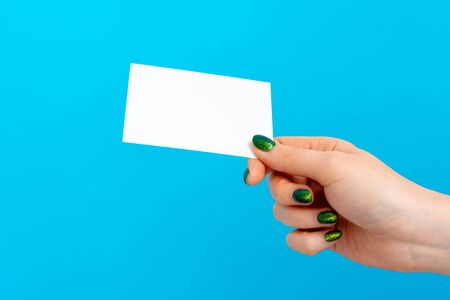 Woman hand holding blank card on blue background, close up.