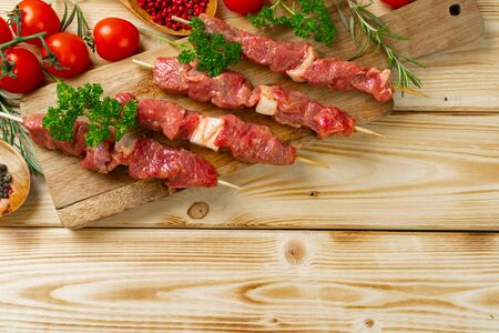 Raw kebab from meat on a wooden background with vegetables.