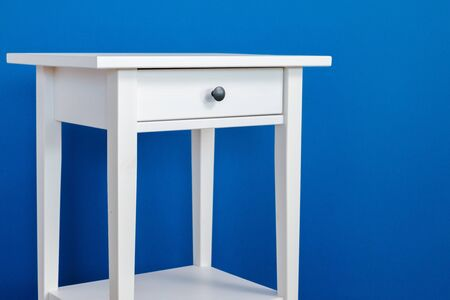 White wooden nightstand table against blue wall Banco de Imagens