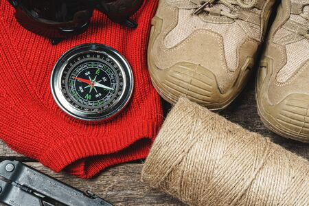 Mountain boots and hiking gear on wooden planks close up