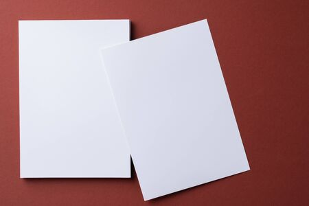 Blank white business cards on burgundy paper background, top view