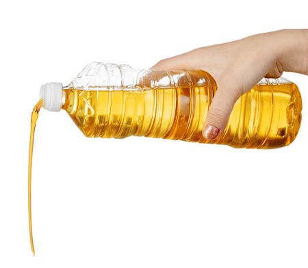 Hand of woman pouring cooking oil from plastic bottle. Isolated on white background. Close up.