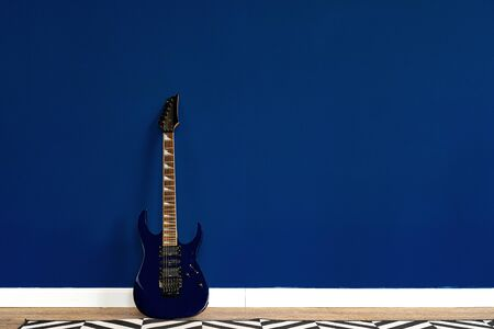 Guitar setup against classic blue wall in apartment