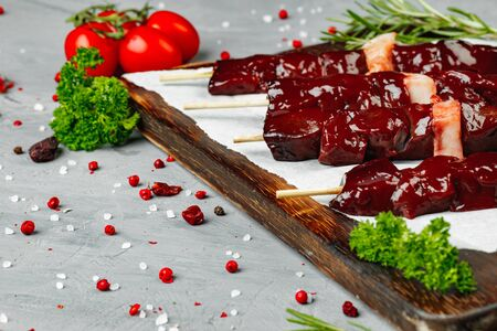 Raw liver kebab on skewers on wooden board