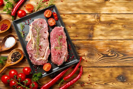 Two raw beef steaks on dark wooden table Banque d'images