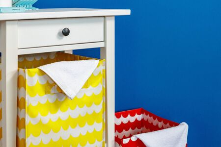 White wooden nightstand with storage box against blue wall Фото со стока