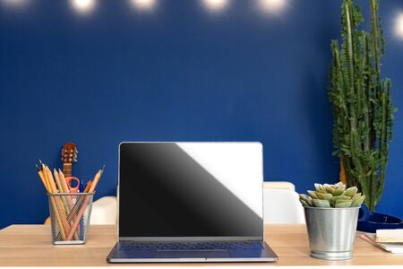 Working table with laptop against blue wall in modern flat Imagens - 148273172