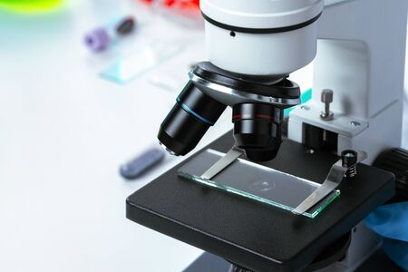 Close up photo of a microscope lenses examining glass sample Standard-Bild