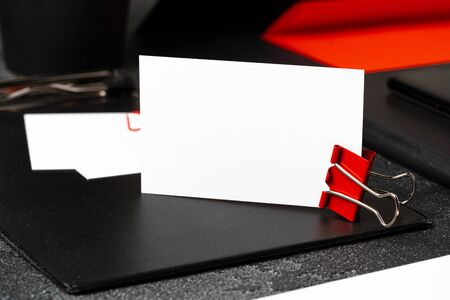 White businesscards united with a paper clip on a black rough background