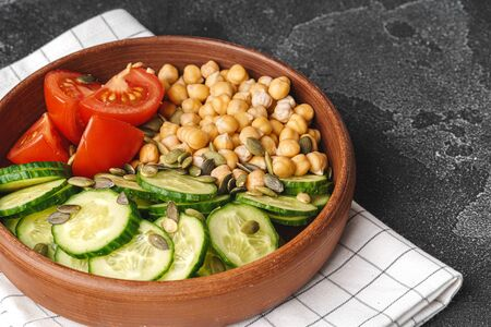 Clay plate of chickpeas and cut cucumbers and tomatoes. Healthy eating Standard-Bild