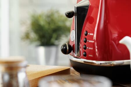 Close up photo of a red toaster on a kitchen table