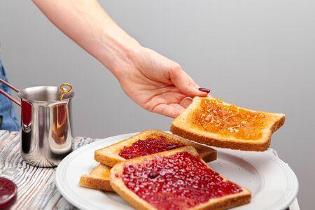 Female hands preparing toasts with fruit jam Zdjęcie Seryjne