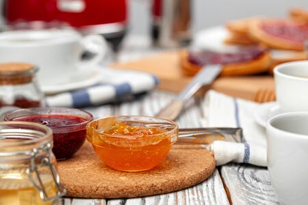 Close up photo of kitchen table with .appliances, kitchenware with toasts and jams. Breakfast