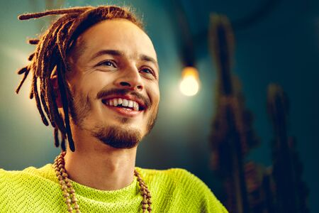Portrait of a positive handsome caucasian guy with dreadlocks against blue background