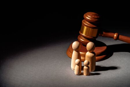 Wooden toy family and judge mallet. Family divorce concept Stock Photo