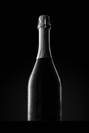 Champagne bottle on black background, copy space