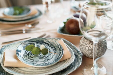 Beautiful elegant table setting with green stylish dishware and silver cutlery