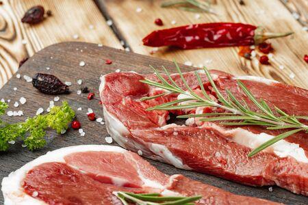 Steaks de viande crue aux herbes sur planche de bois Banque d'images