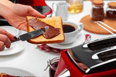 Female hand cooking toast with chocolate paste close up Foto de archivo