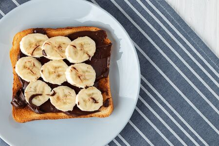Fried toast with chocolate paste and banana slices on blue napkin