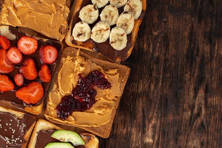 Assortment of sweet sandwiches with chocolate paste, peanut paste, fruit slices and avocado