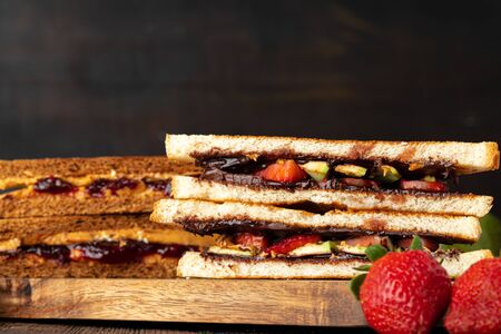 Sandwich toast with chocolate paste and cut strawberry on kitchen table