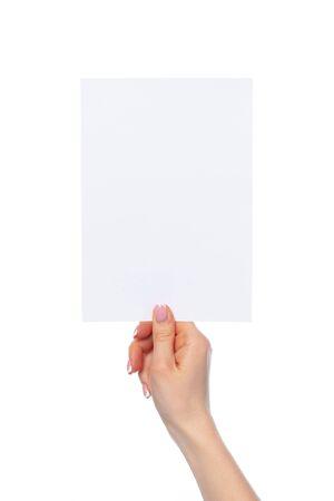 Female hand holding blank white sheet of paper isolated on white background Banco de Imagens
