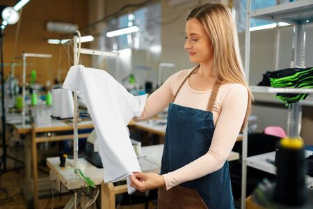 Nice woman tailor holding just sewn t-shirt