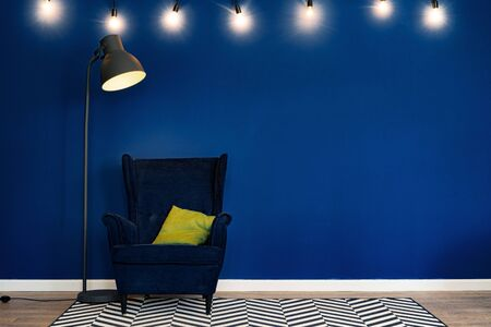 Dark blue arm-chair against blue wall in modern living room. close up. Banque d'images - 150172770