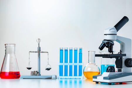 Lab microscope with laboratory glassware on desk
