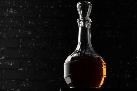 Whisky glass silhouette against dark black grunge wall