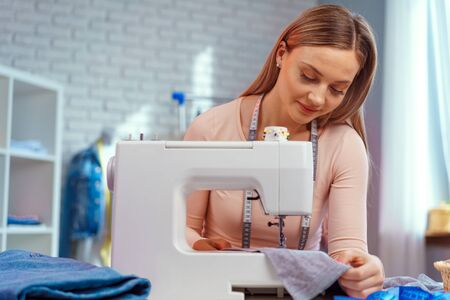 Young seamstress working on her sewing machine on textile factory