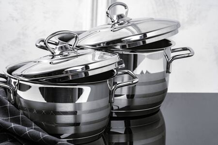 Aluminum cookware on black induction stove against grey wall, copy space