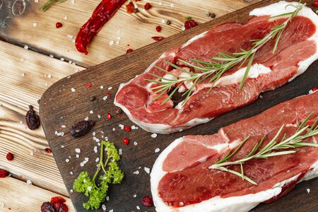 Raw meat steaks with herbs on wooden board