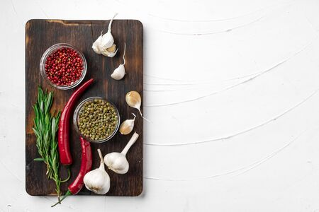 Red chili peppers and other spices on white textured background with copy space, top view