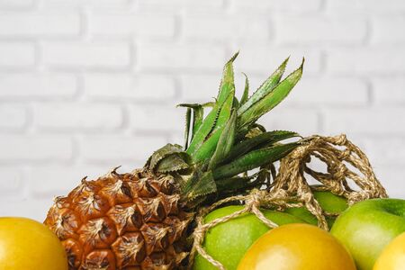 Pineapple, green apples and apricot on table, close up