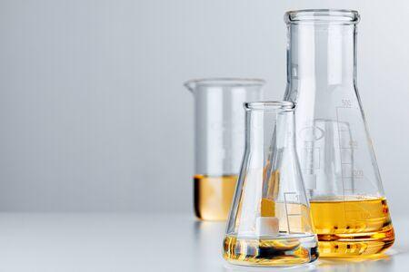 Laboratory glassware with yellow oily liquid on grey background close up 版權商用圖片