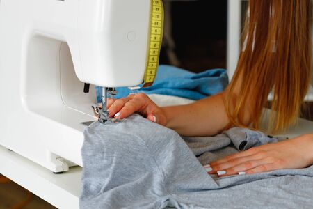 Woman tailor process of stitching on sewing machine close up view