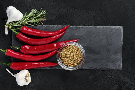 Red hot chili peppers and other spices on dark background, top view