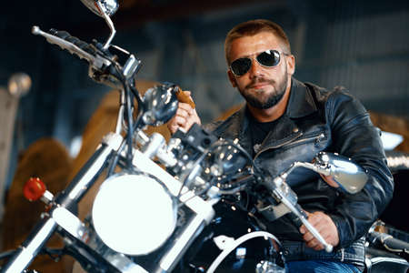 Cool bearded man biker in sunglasses sitting on his motorbike and smoking cigar 스톡 콘텐츠