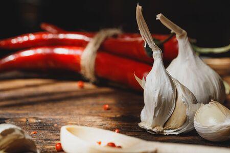 Garlic and chili pepper on dark wooden table Фото со стока
