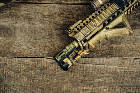 Close up photo of M16 rifle on wooden board close up