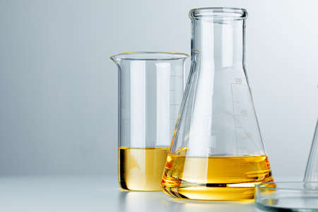 Laboratory glassware with yellow oily liquid on grey background close up Banque d'images