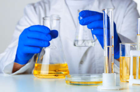 Scientist or doctor in blue gloves pouring some yellow liquid into a flask close up